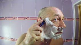 En man i badrummet rakar sk?ggstubben runt om hans tempel med en rakkniv lager videofilmer