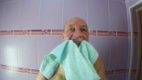 En man i badrummet torkar hans framsida med en rakvattenhandduk lager videofilmer