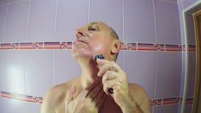 En man i badrumrakningarna med en rakkniv kvarlevorna av vegetation från hans kinder och haka stock video
