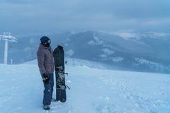 En man i bergen Snowboard i hand sport Snowboarder royaltyfri foto