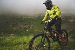 En man i en berghjälm som rider en mountainbike, rider runt om den härliga naturen i molnigt väder sluttande Royaltyfri Bild