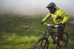 En man i en berghjälm som rider en mountainbike, rider runt om den härliga naturen i molnigt väder sluttande Arkivfoto