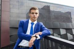 En man i en blå dräkt mot en bakgrund av mörk modern arkitektur Arkivfoto