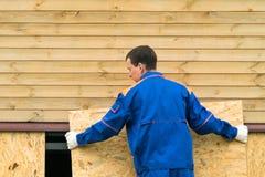 En man i en blå jumpsuit stänger botten av huset med en träsköld royaltyfri bild