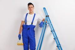 En man, i en blå likformig som lutar hans armbågar på en stege som rymmer en konstruktionsrulle arkivfoton