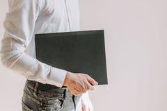 En man i en blå skjorta rymmer en mapp arkivfoton