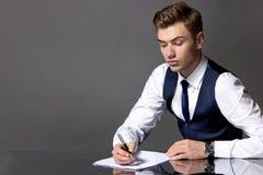 En man i en blått waistcoat och band sitter på en tabell och skriva arkivbild