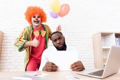 En man i en clowndräkt står bredvid en svart man som sitter på hans skrivbord arkivfoton