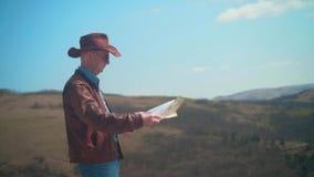 En man i en cowboyhatt, piskar omslaget, jeans, och exponeringsglas st?r i bergen som betraktar en handelsresande?versikt stock video