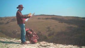 En man i en cowboyhatt, piskar omslaget, jeans, och exponeringsglas st?r i bergen som betraktar en handelsresande?versikt arkivfilmer
