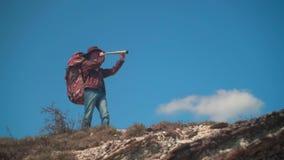 En man i en cowboyhatt, piskar omslaget, jeans, en turist- ryggsäck på hans skuldror En man ser till och med ett teleskop lager videofilmer