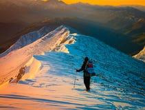 En man i den unika bergsolnedgångvintern! Arkivfoton