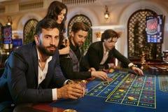 En man i en dräkt med ett exponeringsglas av whisky som sitter på tabellrouletten som spelar poker på en kasino arkivbild