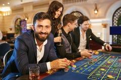 En man i en dräkt med ett exponeringsglas av whisky som sitter på tabellrouletten som spelar poker på en kasino royaltyfri bild