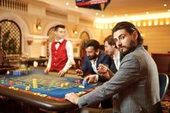 En man i en dräkt med ett exponeringsglas av whisky som sitter på tabellrouletten som spelar poker på en kasino arkivfoto