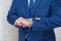 En man i en dräkt ser hans klocka fotografering för bildbyråer