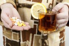 En man i en dressingkappa rymmer preventivpillerar för en handfull och ett varmt te med en citron begrepp: sjukdom förkylning Royaltyfri Foto