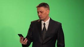 En man i en affärsdräkt bläddrar till och med nyheterna på din smartphone arkivfilmer