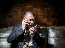 En man i en affärsdräkt talar känslomässigt på smartphonen två Fotografering för Bildbyråer