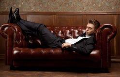 En man i en dräkt som ligger på soffan royaltyfri foto