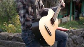 En man i en skjorta och jeans som spelar gitarren arkivfilmer