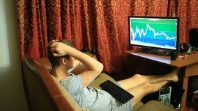 En man i en T-tröja och kortslutningar som hemma sitter på soffan, övervakar ändringar i schemat på valutautbytet lager videofilmer