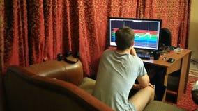En man i en T-tröja och kortslutningar som hemma sitter på soffan, övervakar ändringar i schemat på valutautbytet arkivfilmer
