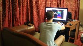 En man i en T-tröja och kortslutningar som hemma sitter på soffan, övervakar ändringar i schemat på valutautbytet stock video