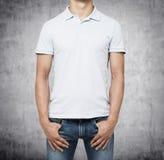 En man i en vit poloskjorta och grov bomullstvill rymmer hans händer i fack Arkivbilder