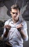 En man i en vitt skjorta och band bryter kedjan Arkivfoto