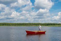En man i ett fartyg, i mitten av sjön, rymmer en fiska pol för att fånga fisken, mot bakgrunden av en härlig himmel arkivbilder