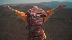 En man i ett gult omslag, exponeringsglas och en turist- ryggsäck står i berg, lyfter upp hans händer, ett symbol av frihet stock video
