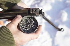 En man i ett kamouflageomslag som rymmer ett BBvapen och en ask av rådjurshagel, ammunition royaltyfria bilder