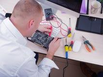 En man i ett kontor i en vit skjorta reparerar ett videokort Cryptocurrency arkivfoto