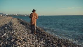 En man i ett lång lag och hatt promenerar kusten, vågor slår lager videofilmer