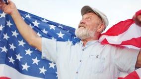 En man i ett lock firar USA-självständighetsdagen på Juli 4th En äldre man med ett grått skägg som rymmer en USA-flagga på hans arkivfilmer