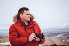 En man i ett rött klår upp ner med resor för en kamera till bergen i vinter royaltyfri foto