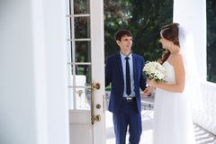 En man i ett stilfullt benigt för affär öppnar försiktigt dörren till en trevlig flicka i en bröllopsklänning och en bukett av bl royaltyfri fotografi