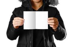 En man i ett varmt vinteromslag som rymmer en vit broschyr blankt papper close upp bakgrund isolerad white arkivfoto