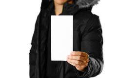 En man i ett varmt vinteromslag som rymmer en vit broschyr blankt papper close upp bakgrund isolerad white royaltyfria bilder