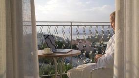 En man i ett vitt labblag arbetar på en bärbar dator på terrassen som förbiser fjärden 4K stock video