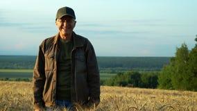 En man i exponeringsglasskratt som står på ett vetefält på en sommardag arkivfilmer