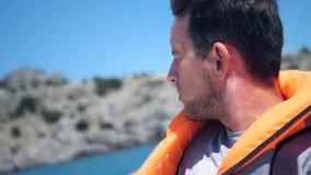 En man i en flytväst seglar på ett fartyg längs kusten HD 1920x1080 långsam rörelse lager videofilmer