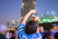 En man i folkmassan fotograferar den Dubai horisonten Royaltyfria Bilder