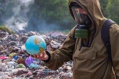 En man i en gasmask ser när den härliga planetjorden På bakgrunden av brinnande plast- avfall Begreppet av environme arkivfoto