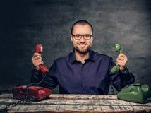 En man i glasögon genom att använda den parallella traditionsmobiltelefonen Royaltyfria Bilder