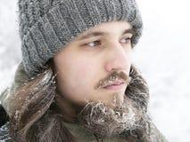 En man i en grå färger stucken hatt, med det frostade skägget och långt hår i vinter Royaltyfria Foton