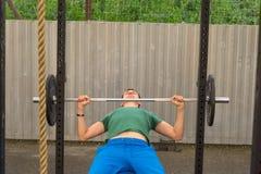 En man i en grön T-tröja och blått flåsar göra en stångbänkpress arkivbild