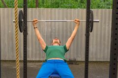 En man i en grön T-tröja och blått flåsar göra en stångbänkpress, arkivfoton