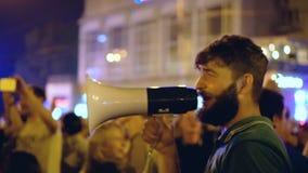 En man i en grön T-tröja under ett gataparti, startat sjunga till ropet lager videofilmer